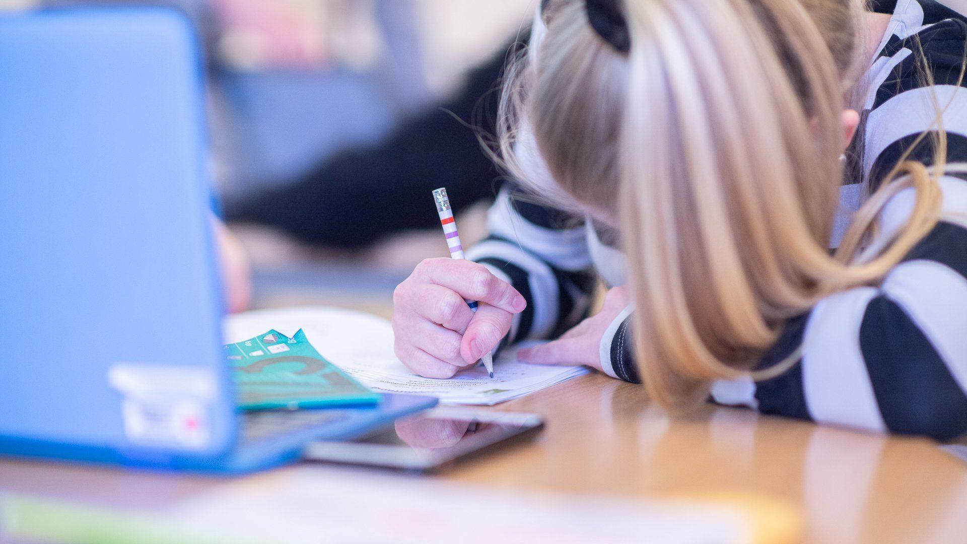 En flicka skriver i ett anteckningsblock framför en laptop