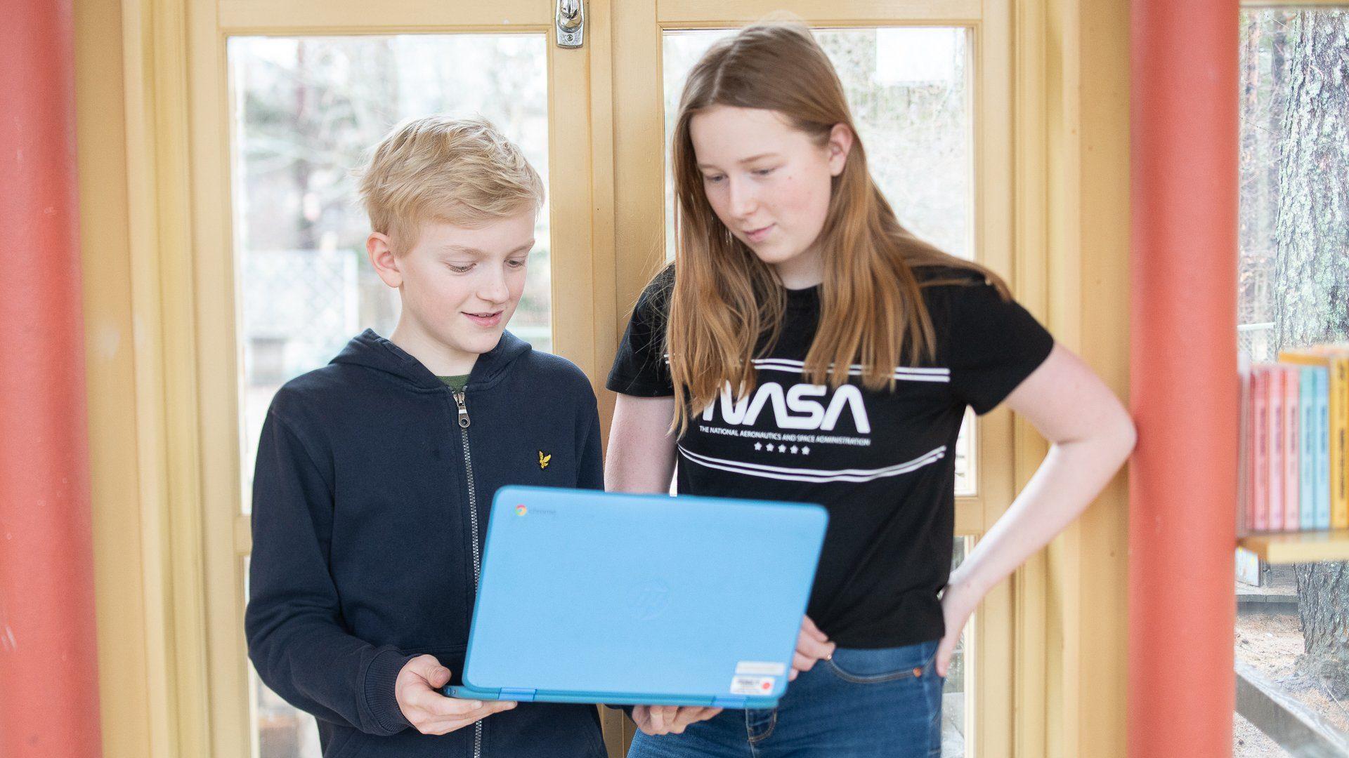 Två elever står i en skolkorridor och tittar på en laptop