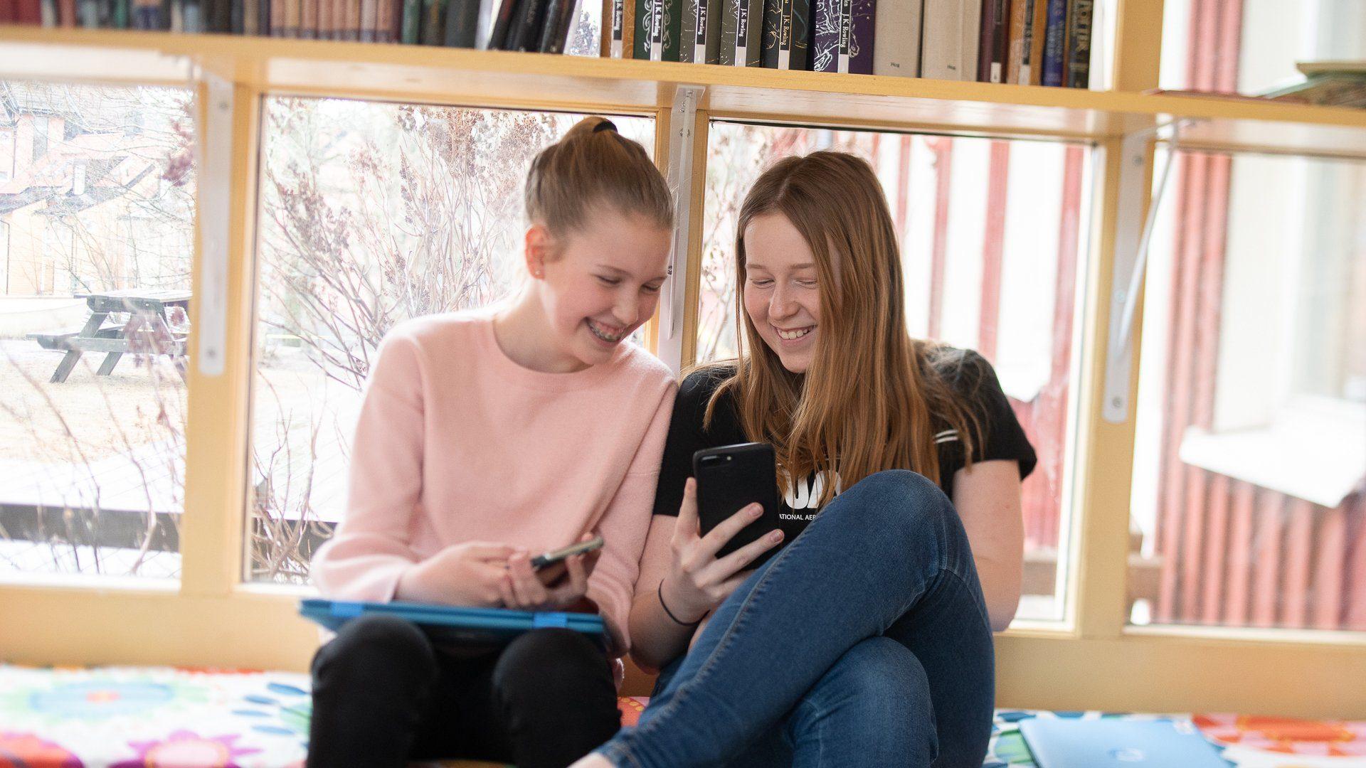 Två flickor tittar på en mobil och skrattar