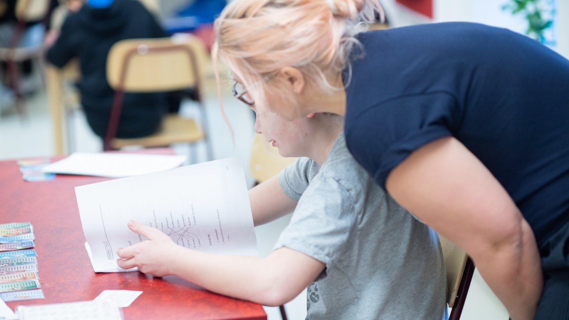 En lärare hjälper en elev med skolarbete