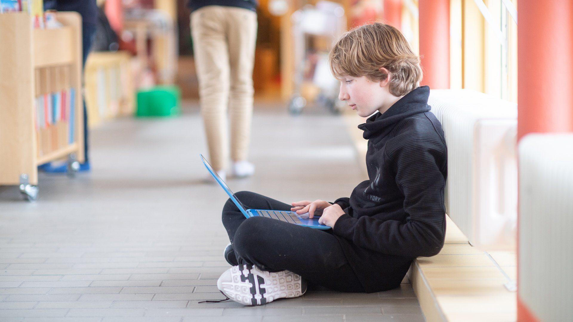 En pojke sitter i skolkorridor med en dator i knät.