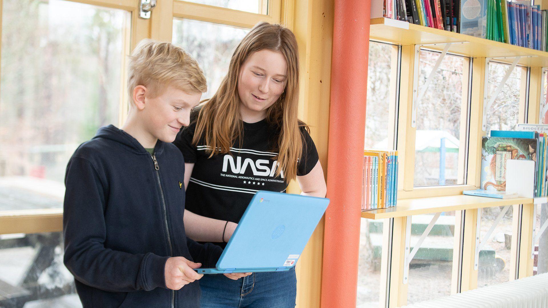 En pojke och en flicka tittar på en bärbar dator i en skolkorridor