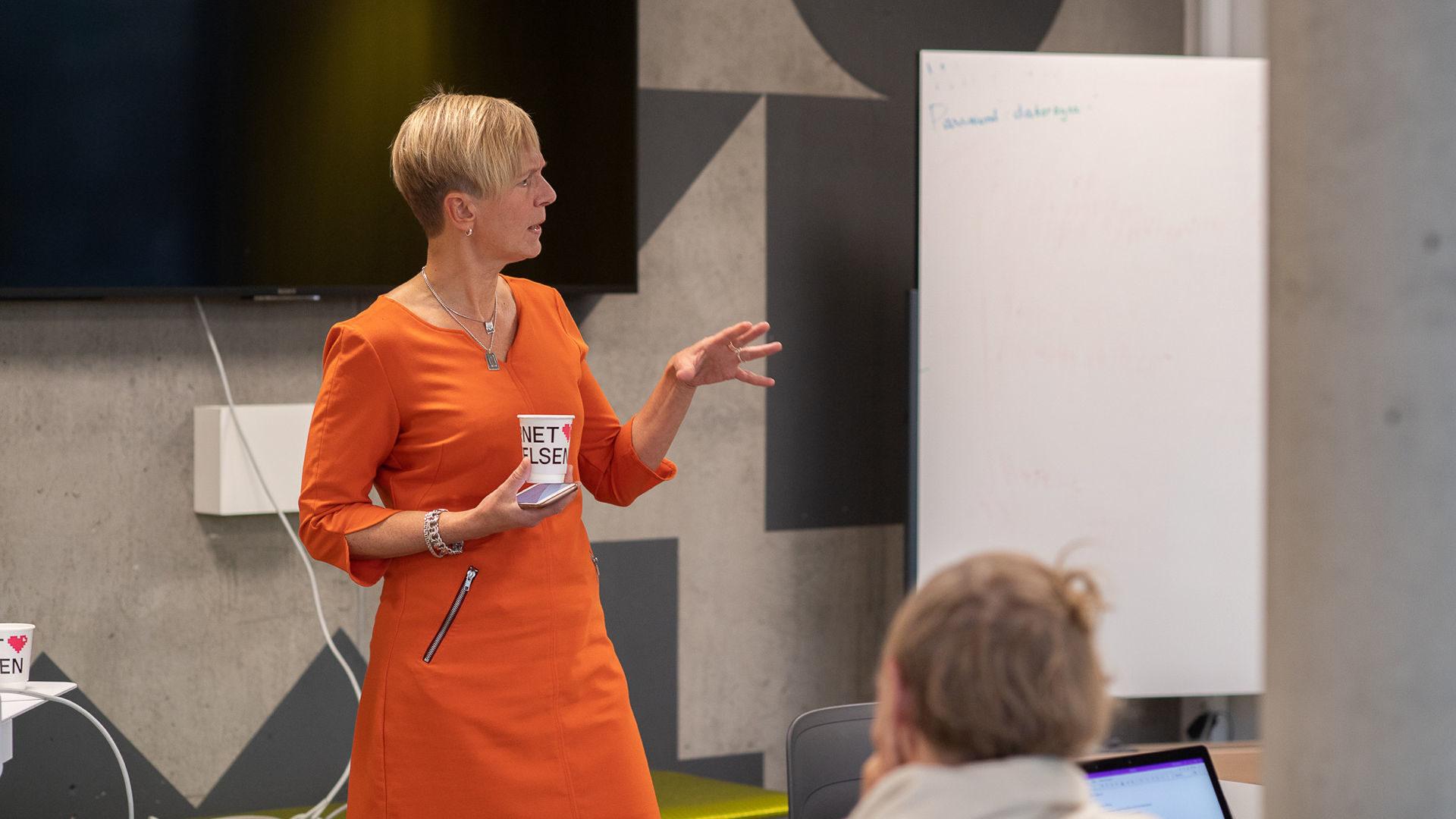 Kvinna med mobil och mugg pratar med publik
