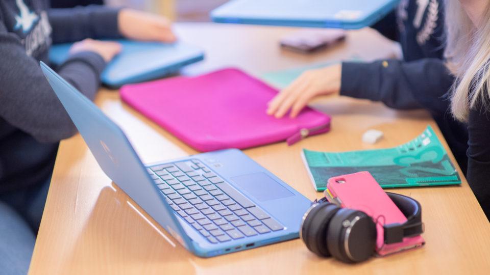 Datorer, mobiltelefoner, hörlurar och datorfodral på skolbänk.