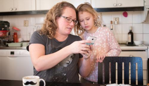 Kvinna visar ett barn något på mobiltelefon vid köksbord.
