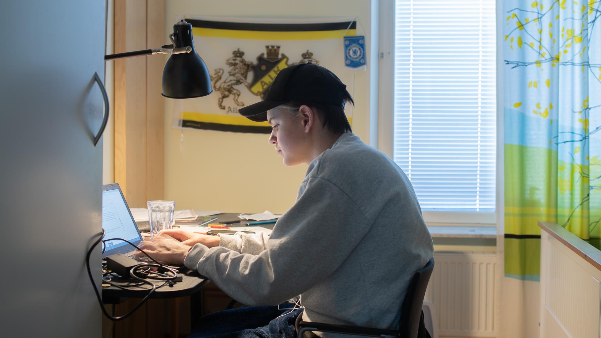 Pojke vid dator arbetar med skola hemma