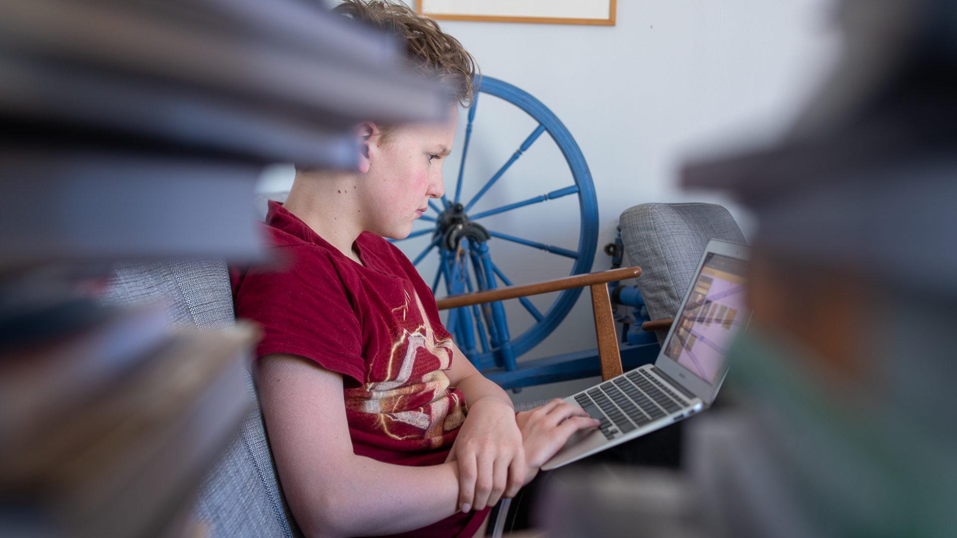 pojke sitter i soffan och arbetar på en laptop