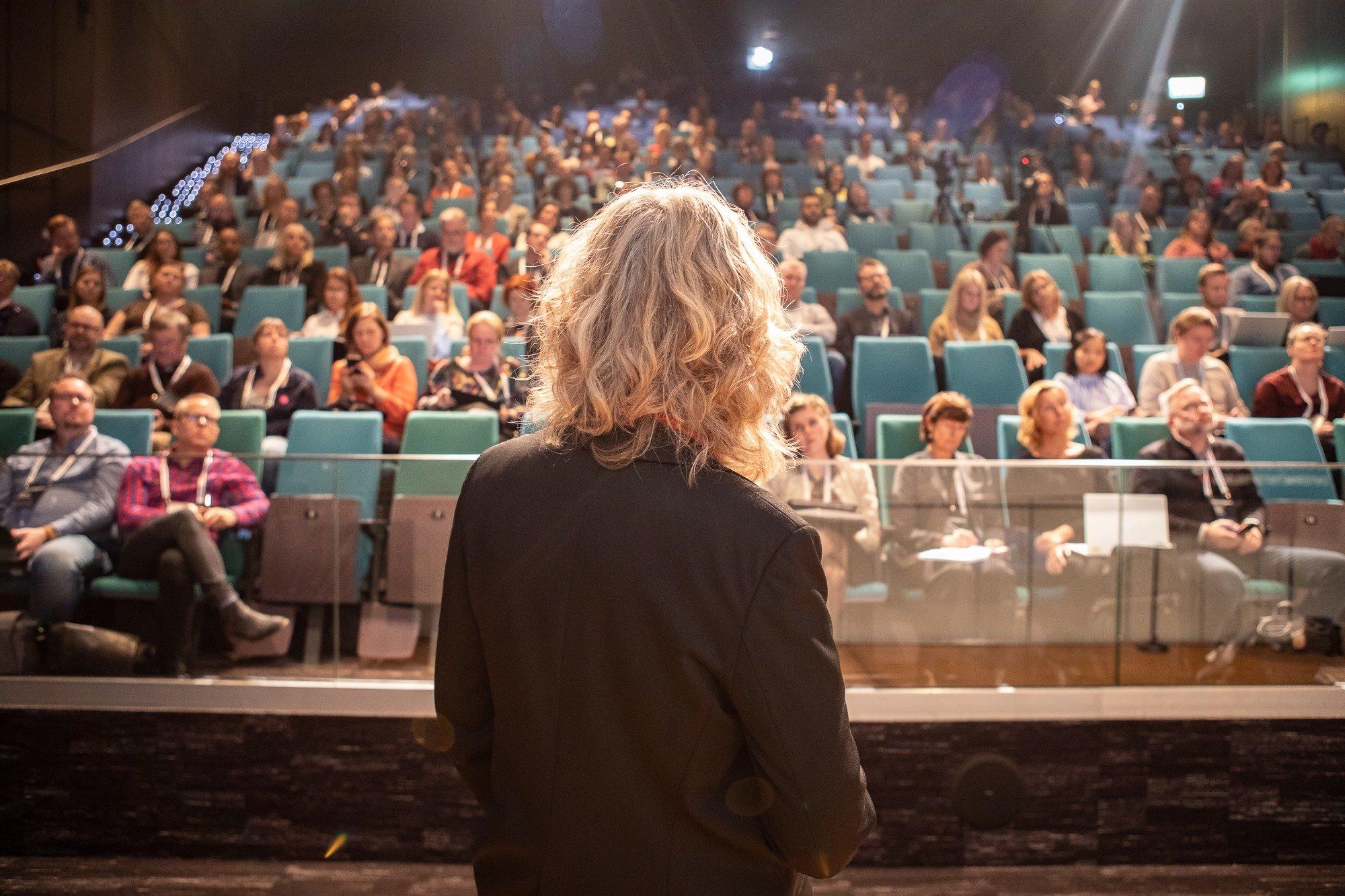 Kvinna som står framför en stor publik
