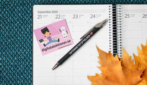 Penna och klistermärke som ligger på en kalender som är uppslagen på september månad.